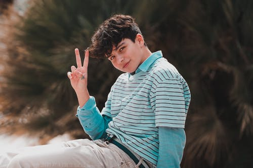 Content young guy showing V sign and smiling