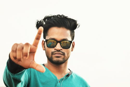 Serious ethnic man showing fingers sign against white background