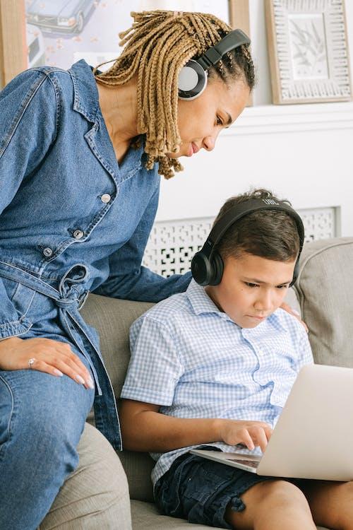 Woman Sitting Beside Boy Using Laptop