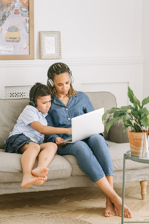 Boy and Woman Sitting on Sofa with Laptop
