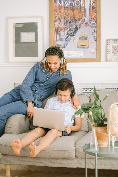 Woman and Young Boy Sitting on Sofa with Laptop and Headphones