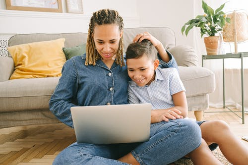 Woman and Young Boy Sitting on Floor with Laptop
