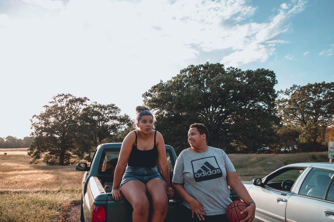 Joyful overweight couple talk near hatchback
