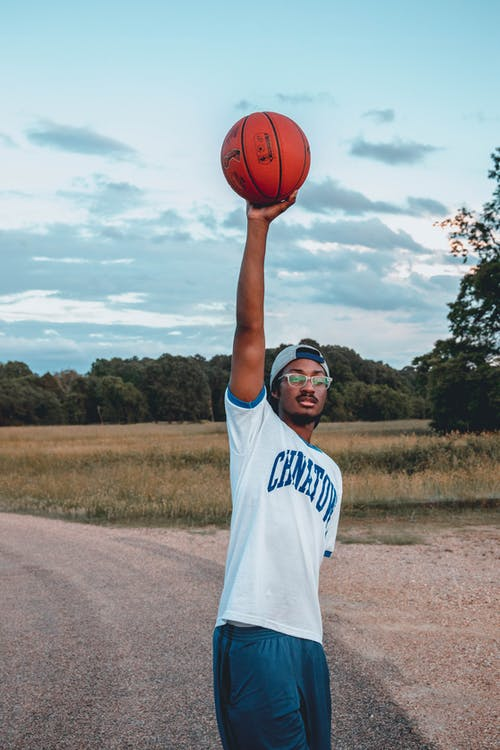Black sportsman with basketball on roadway under cloudy sky