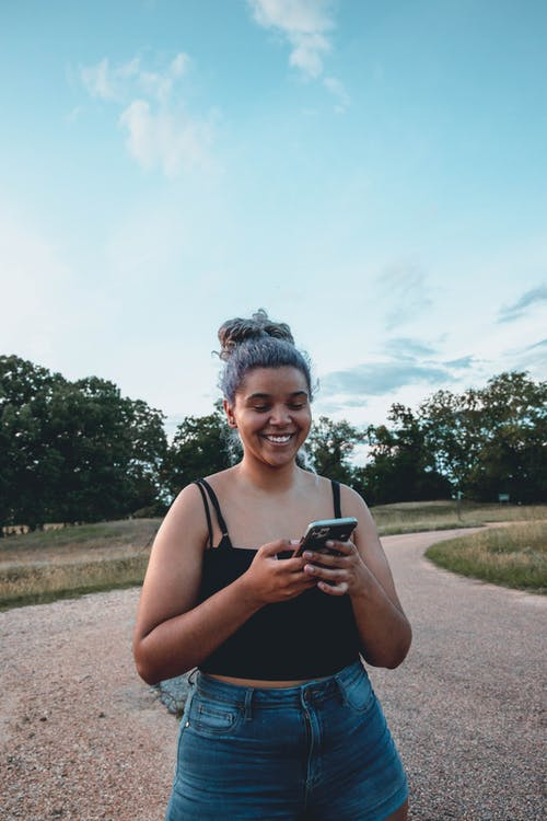 Young cheerful chubby ethnic lady text messaging on cellphone while standing on rough road near park