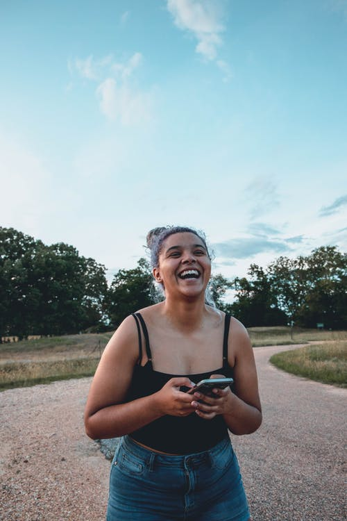 Joyful ethnic woman with smartphone on road