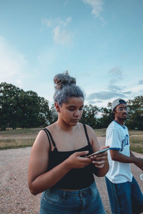Ethnic female browsing internet on cellphone near African American partner on road near park