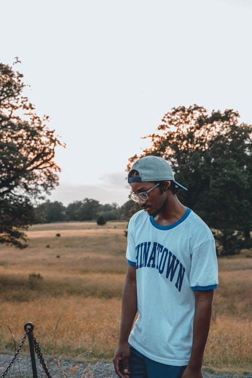 Serious African American male in eyewear and casual clothes pensively looking down while standing in countryside