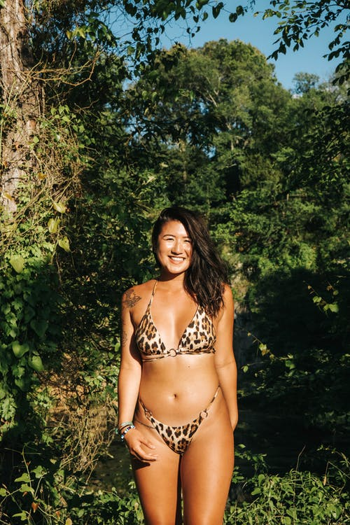 Young Asian lady in swimwear smiling brightly while relaxing among green plants in bright sunny day