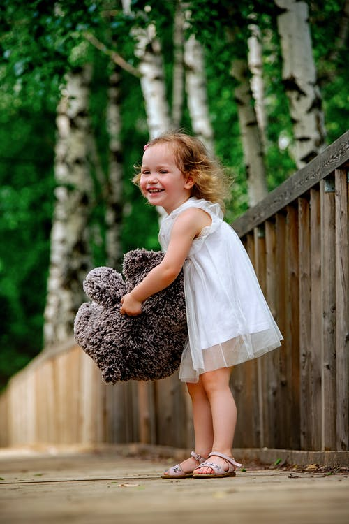 Cheerful little girl with soft bear toy on wooden footpath