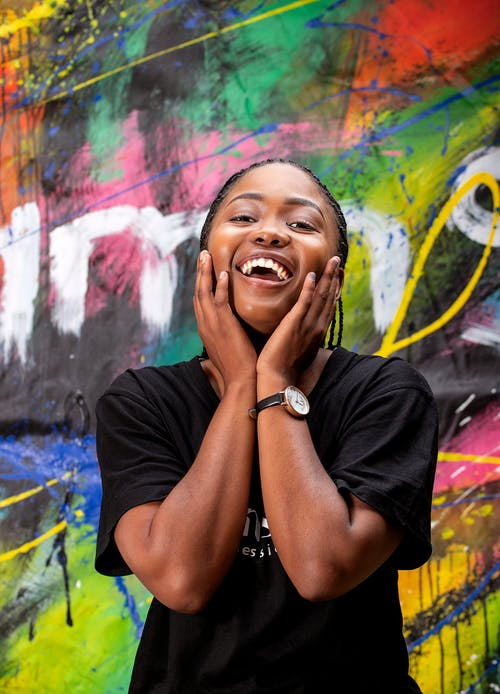Excited black woman touching cheeks against graffiti wall