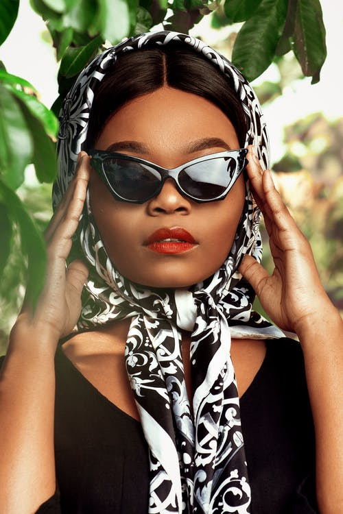 Fashionable African American female in stylish silk headscarf standing near lush tree and touching trendy sunglasses temples