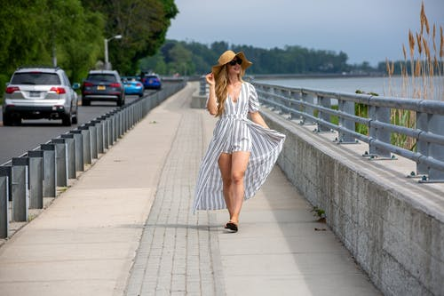 Full body positive young female wearing trendy maxi dress and hat strolling along embankment near busy road and enjoying sea view