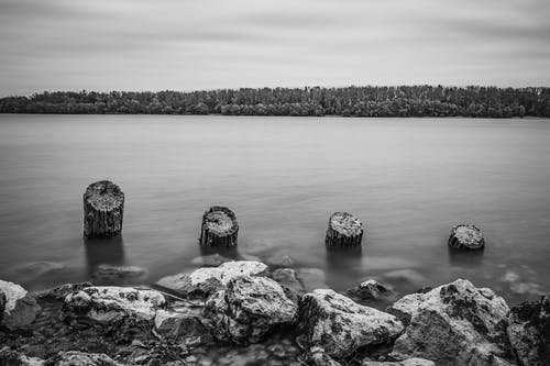 Grayscale Photo of Rocks on Body of Water