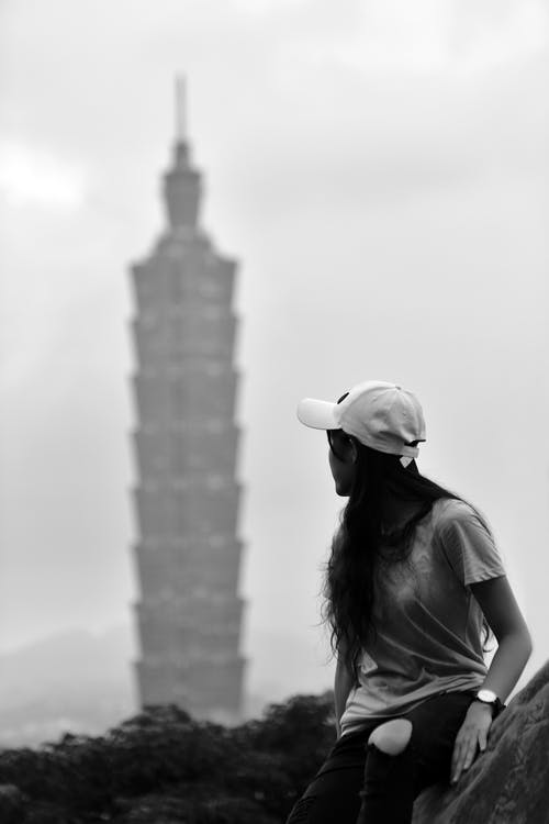 Grayscale Photography of Woman Looking at the Tower