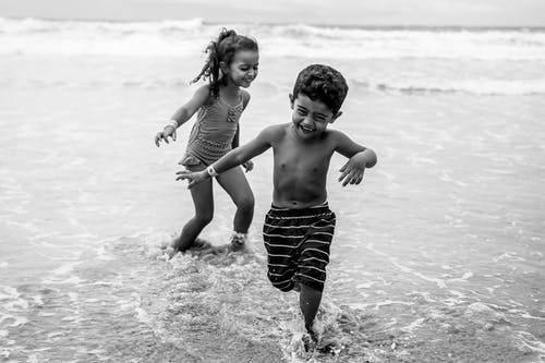 Black and white of cheerful ethnic boy and girl in swimwear running on wavy ocean water during summer trip
