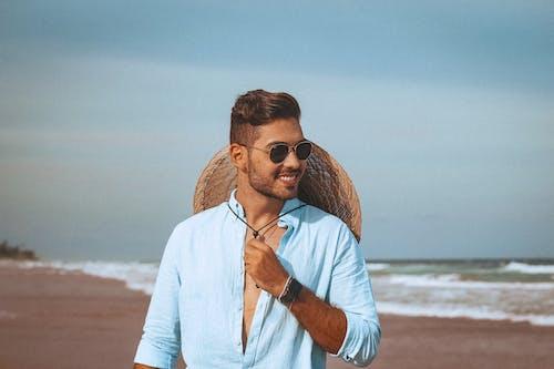 Happy male tourist in sunglasses on beach near wavy sea