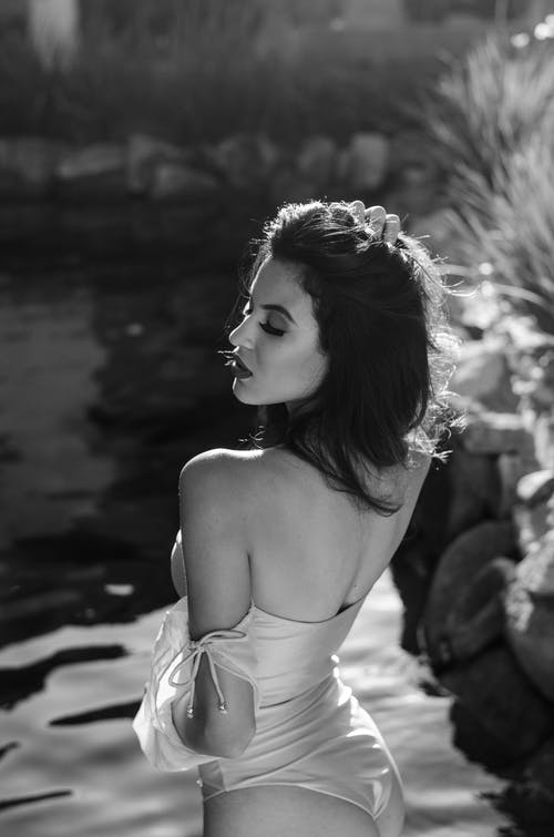 From above black and white back view of young seductive woman in trendy swimwear with makeup and closed eyes near rippled pond