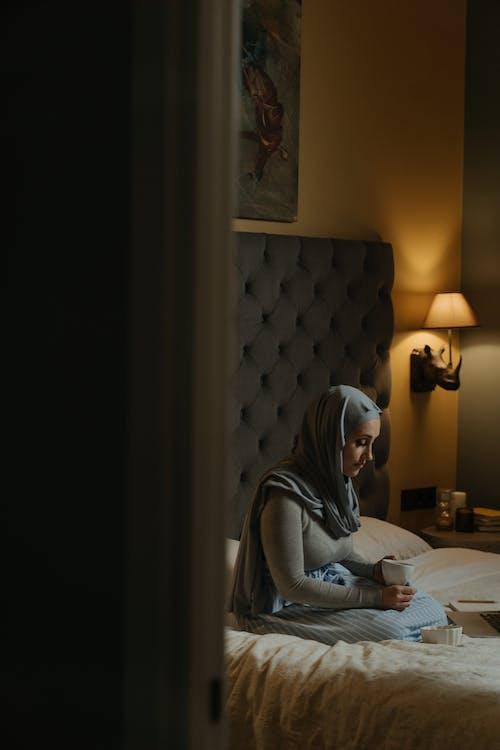 Kobieta W Szarym Hidżabie Siedzi Na łóżku Za Pomocą Laptopa