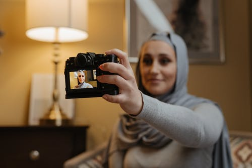 Woman in Gray Sweater Holding Black Camera