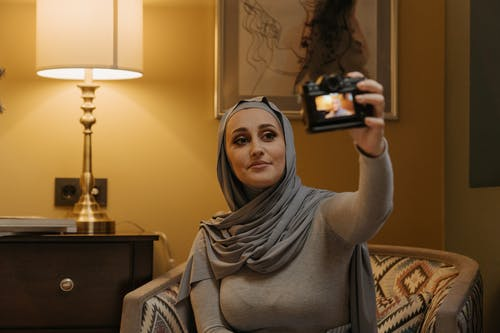 Woman in Gray Hijab Holding Black Smartphone