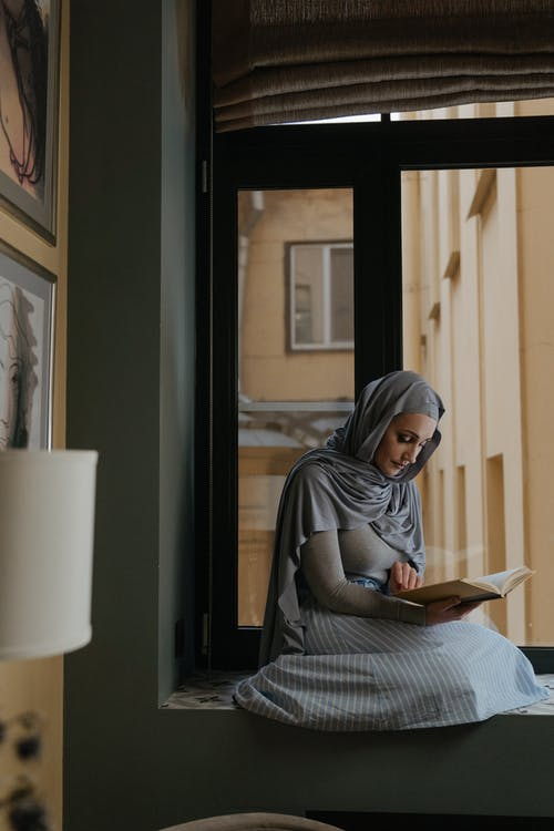 Woman in Gray Hijab Reading Book
