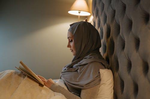 Woman in Brown Hijab Sitting on Brown Wooden Chair