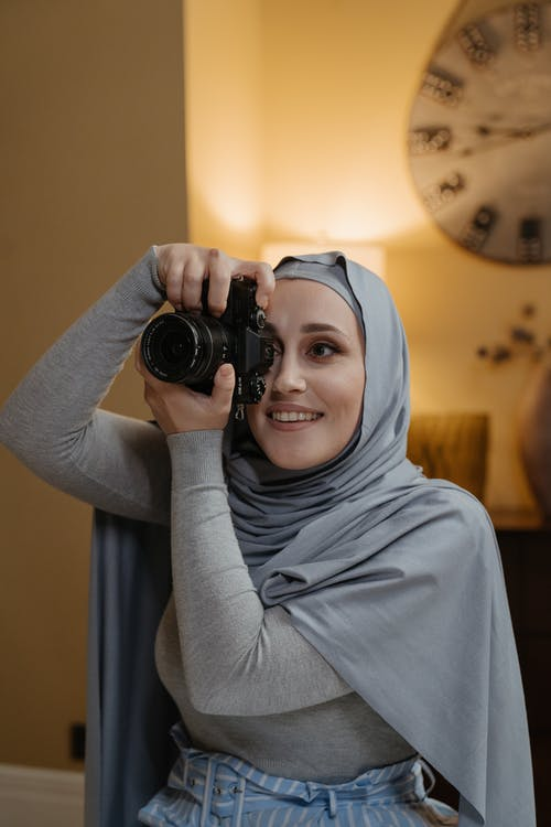 Woman in Gray Hijab Holding Black Dslr Camera
