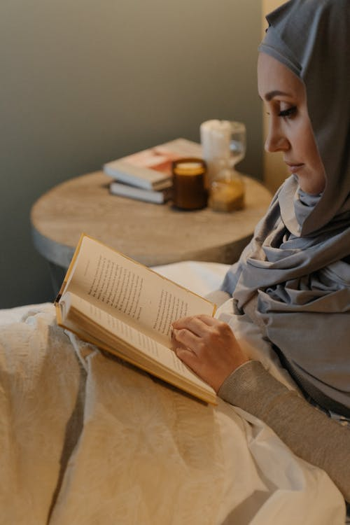 Woman in Gray Robe Reading Book