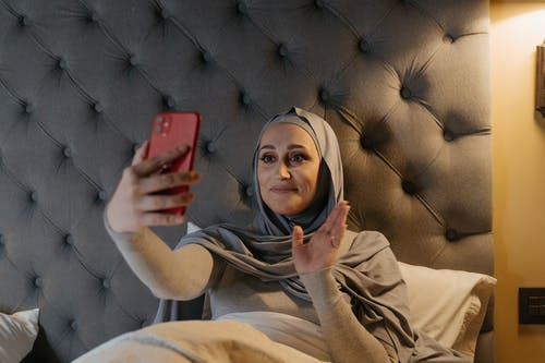 Woman in Brown Hijab Holding Red Smartphone