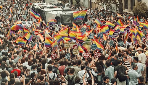 Crowd of anonymous people walking on street and waving rainbow flags during gay parade in city