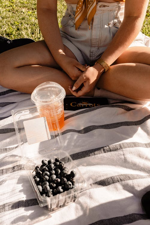 Crop woman with beverage and blueberries during picnic