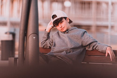 Charming stylish male teenager in hoodie and cap sitting on wooden bench while leaning on hand and looking at camera