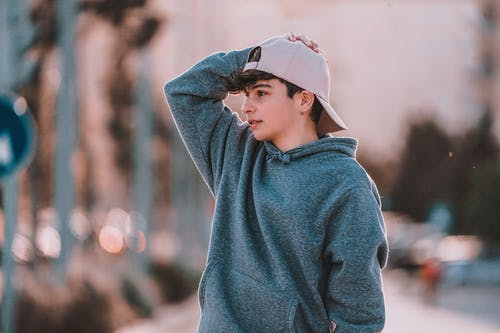 Contemplative male adolescent in stylish clothes with cap looking away in town in daytime