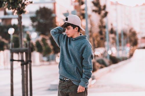 Wistful teenager in trendy apparel on street