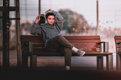 Pondering male teenager in trendy clothes with cap touching hair while sitting with crossed legs on bench and looking at camera