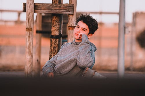Dreamy teenager in stylish clothes resting on bench