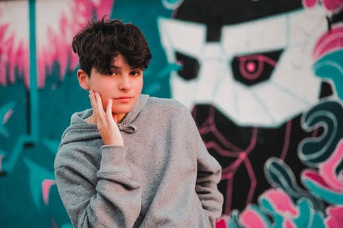 Trendy male teenager in modern hoodie touching cheek while looking at camera behind bright graffiti wall