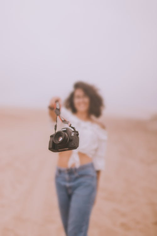 Woman in White Long Sleeve Shirt and Blue Denim Jeans Holding Black Dslr Camera