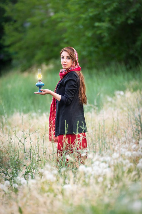 Side view of young feminine lady in bright ornamental wear with shiny candlestick looking at camera on lawn
