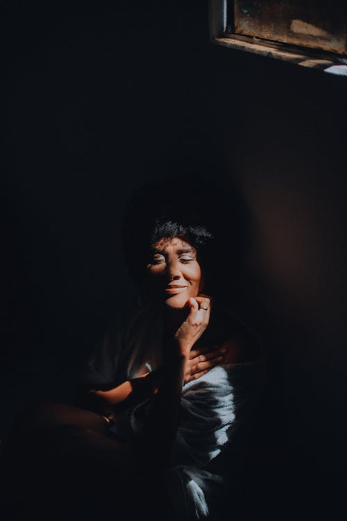 Stylish smiling dreamy ethnic woman with closed eyes in darkness