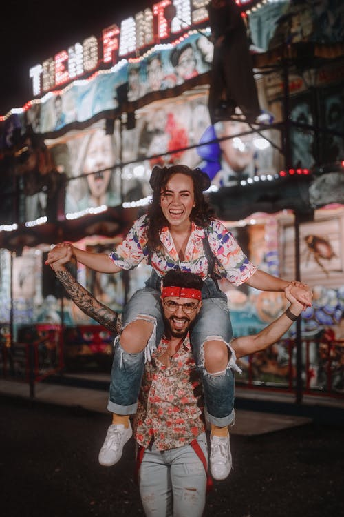 Happy man carrying cheerful girlfriend on shoulders in town