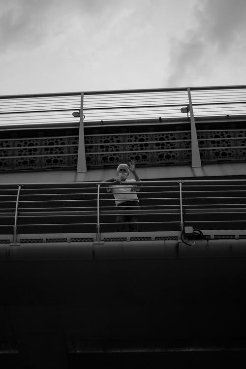 Grayscale Photo of Woman Sitting on the Stairs