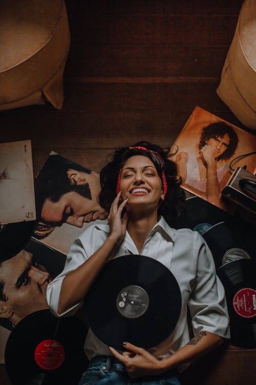 Stylish cheerful woman with collection of vinyl records at home