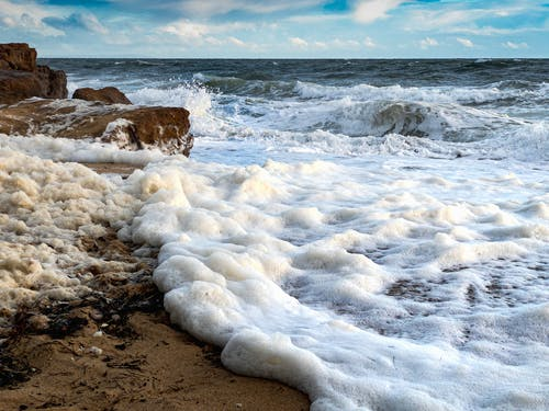 Scenic view of foamy ocean waves rolling on rough rocky coast against clear blue sky