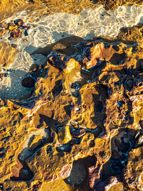 Top view abstract textured background of brown rocky surface under clear transparent water