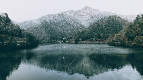 Picturesque landscape of snowy forested hills near calm lake