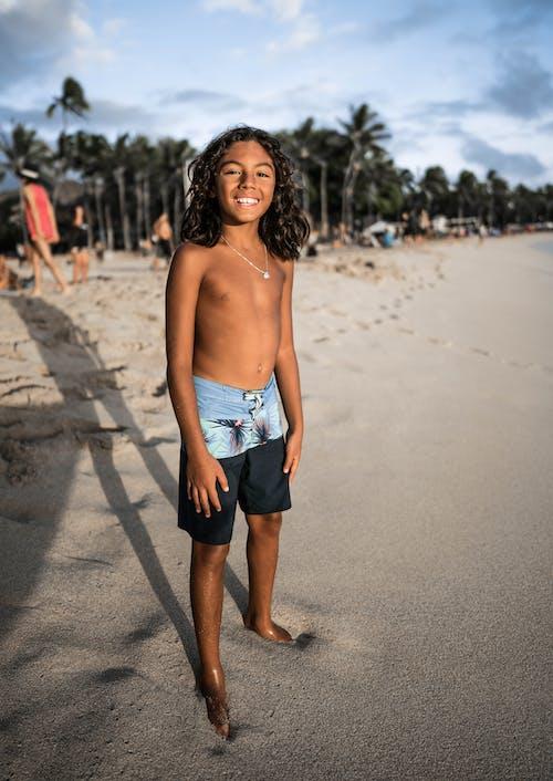 Happy Hispanic boy standing on sandy beach
