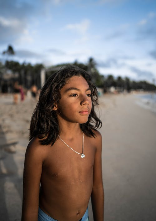 Calm Hispanic boy standing on sandy seashore