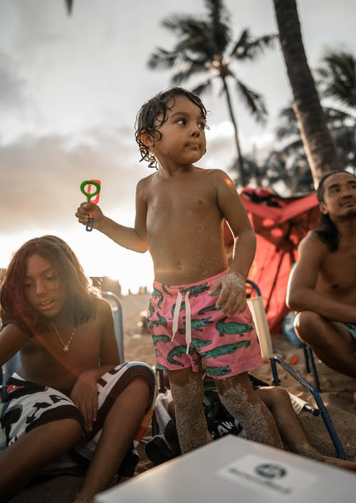 Positive Hispanic boy with toy spending summer day with natives on sandy beach and looking away contentedly
